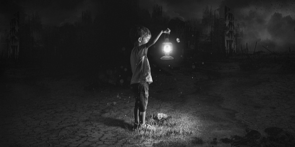 Boy holding  a lantern in the dark