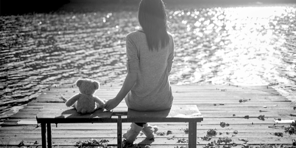 lady on the bench with teddy bear watching a lake
