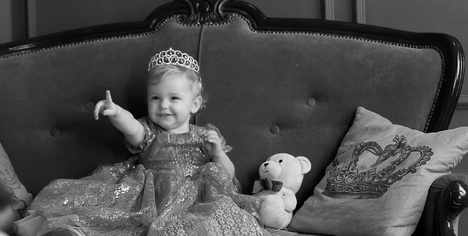 Little girl dressed in princess with teddy bear on a couch