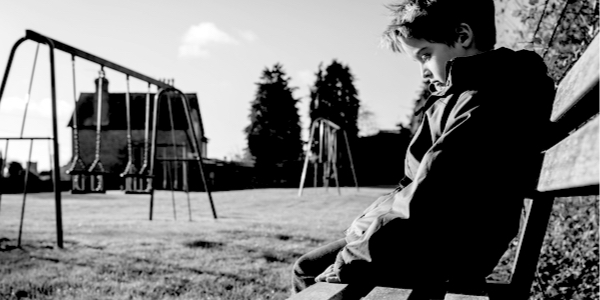 boy alone on a bench in a park