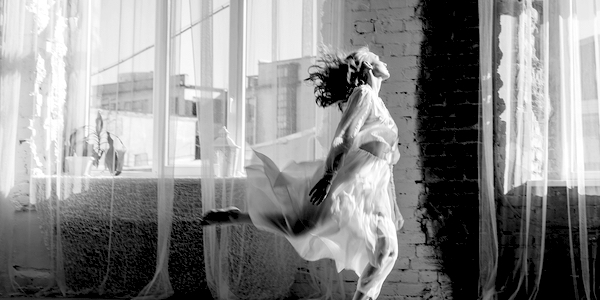 Female dancing in front of a window