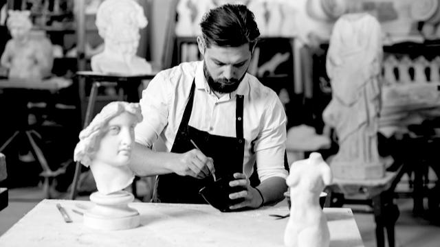Sculptor man focused on making his art