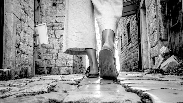Female feet walking on cobblestone street toward a painting isle