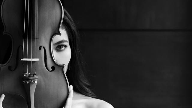Female musician hiding behind a violin