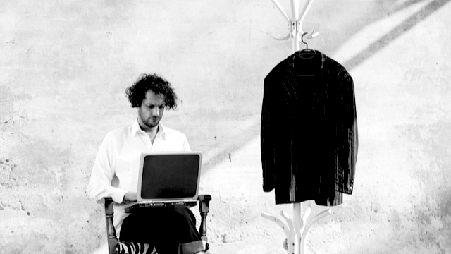 Man writer next to a his coat on a hanger - imperfect artistic life concept