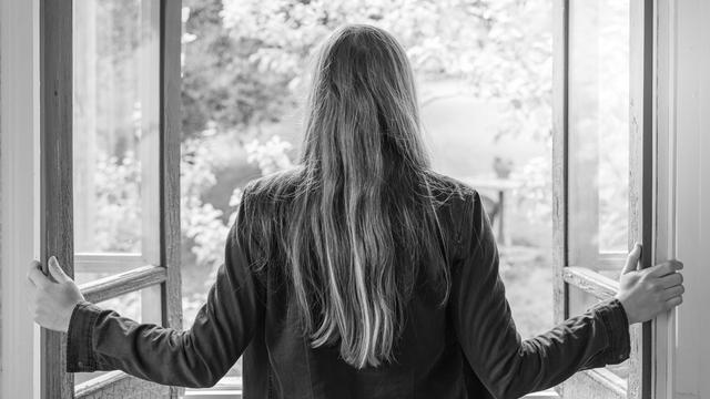 Female opening a window looking outside