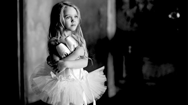 Little ballerina girl holding her ballet shoes