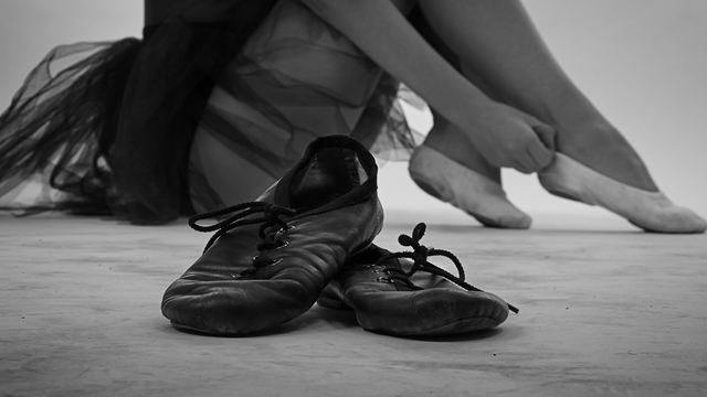 Ballerina sitting on the floor next to her ballet shoes