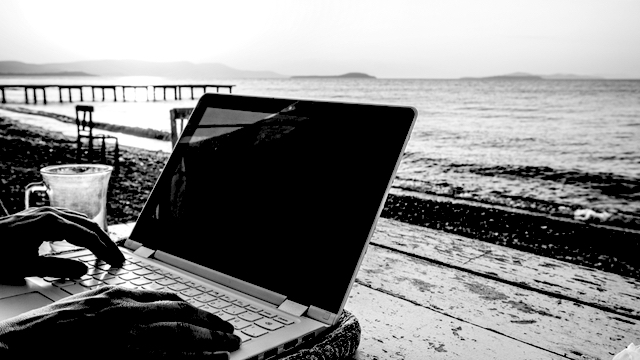 Hands of a female writer on a laptop - on a table at the beach.