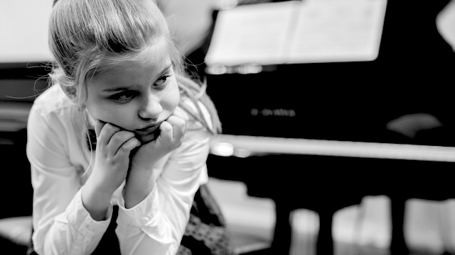 Little girl disappointed in front of a piano
