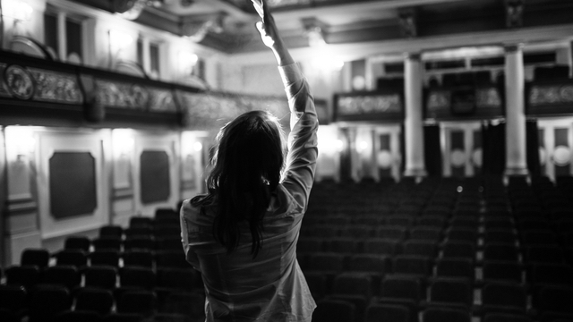 Female performer alone, performing, in a empty theater.