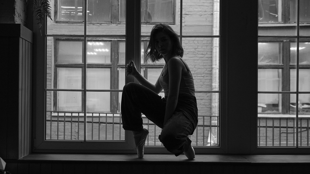 Female young dance practicing in front of her window at home