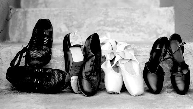 Different dance shoes - ballet, tap, flamingo, sports - left alone, empty.